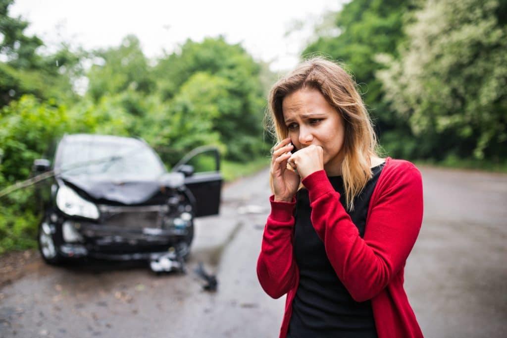 Una giovane donna con lo smartphone dall'auto danneggiata dopo un incidente d'auto, facendo una telefonata.