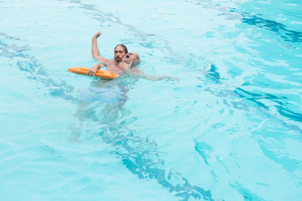 Lifeguard rescuing senior man from swimming pool