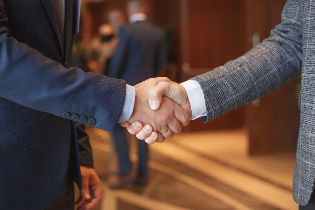Gli uomini si stringono la mano alla riunione d'affari sos diritti