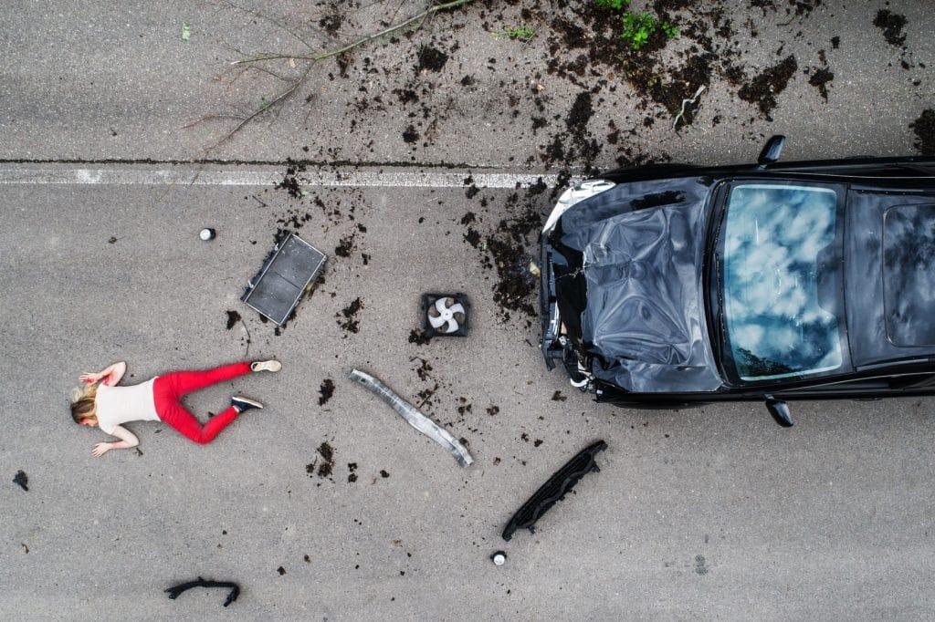 Giovane donna ferita che si trova sulla strada dopo un incidente d'auto, incosciente.